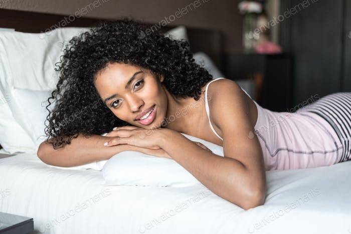 black woman happy on bed smiling and stretching looking at camer