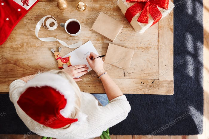 Overhead Shot Looking Down On Woman Writing In Christmas Card And Wrapping Gift Wearing Santa Hat