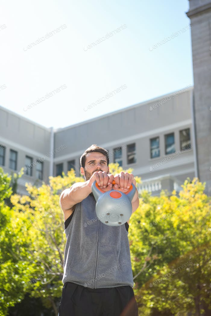 Handsome athlete lifting kettle bell in the city