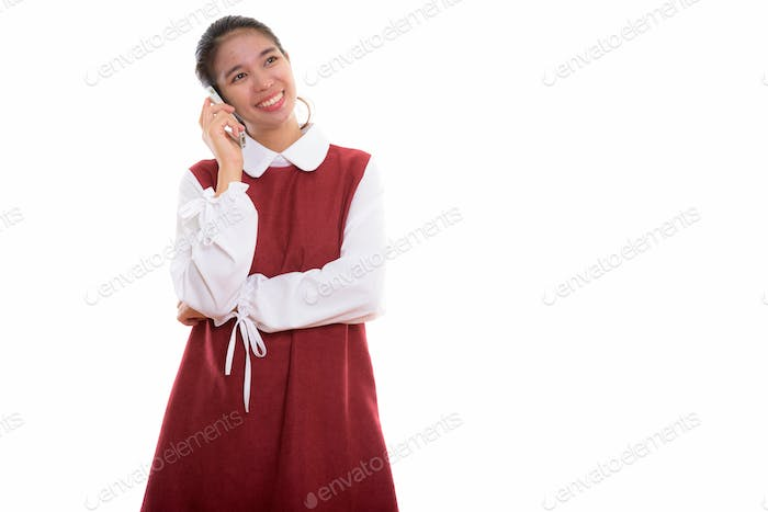 Studio shot of young happy Asian woman using phone