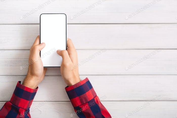 Man messaging on smartphone with blank screen over wooden background
