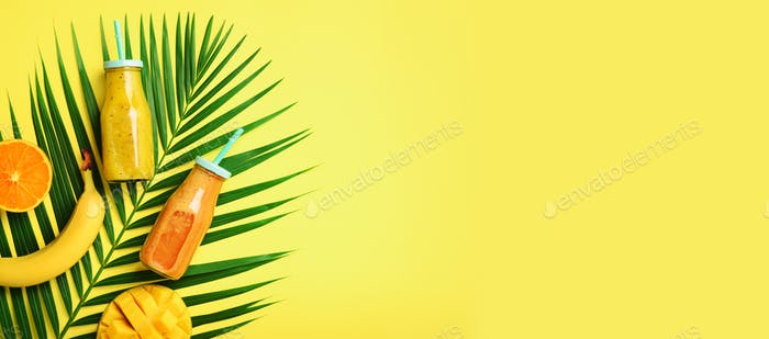 Exotic orange, banana, pineapple, mango smoothie and juicy fruits on palm leaves over yellow