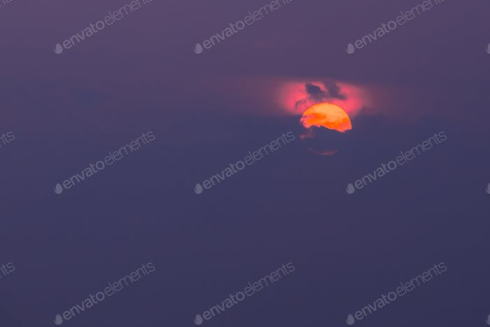 Close View Of Orange Sun Disk Partly Covered By Clouds With Crim