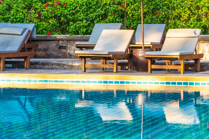 Umbrella and chair around swimming pool in hotel resort neary se