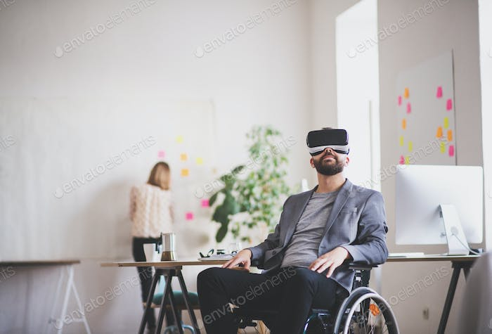 Two business people with wheelchair and VR goggles in the office.