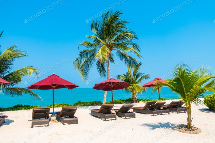 Beautiful tropical beach sea ocean with umbrella and chair around coconut palm tree on blue sky