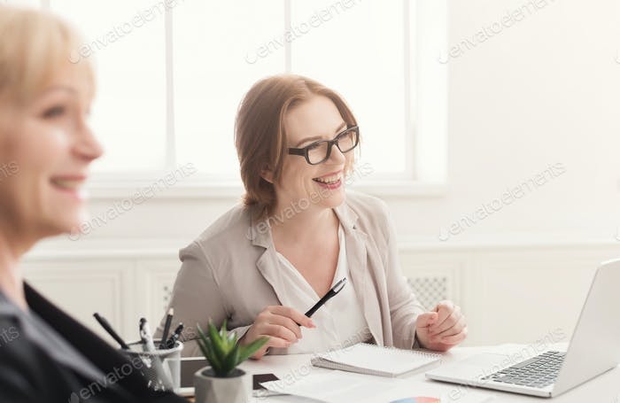 Two happy women working together in modern office