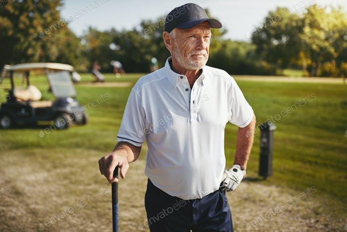 Senior Mann Blick auf die Fairway eines Golfplatzes