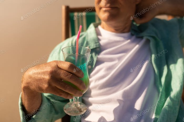 Mid section of senior man having cocktail drink while relaxing on sun lounger at beach