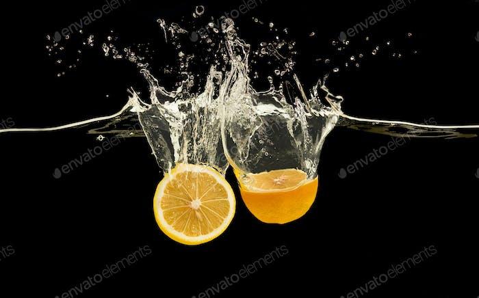 Reife Orangenhälften fallen ins Wasser