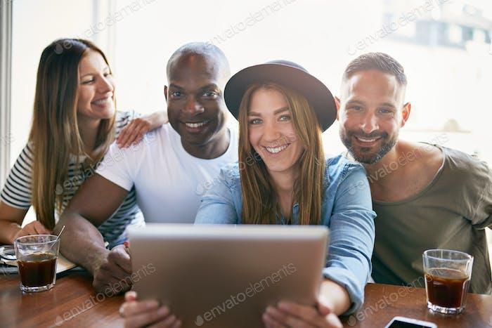 Gruppe von lächelnden Menschen sitzen mit Tablet