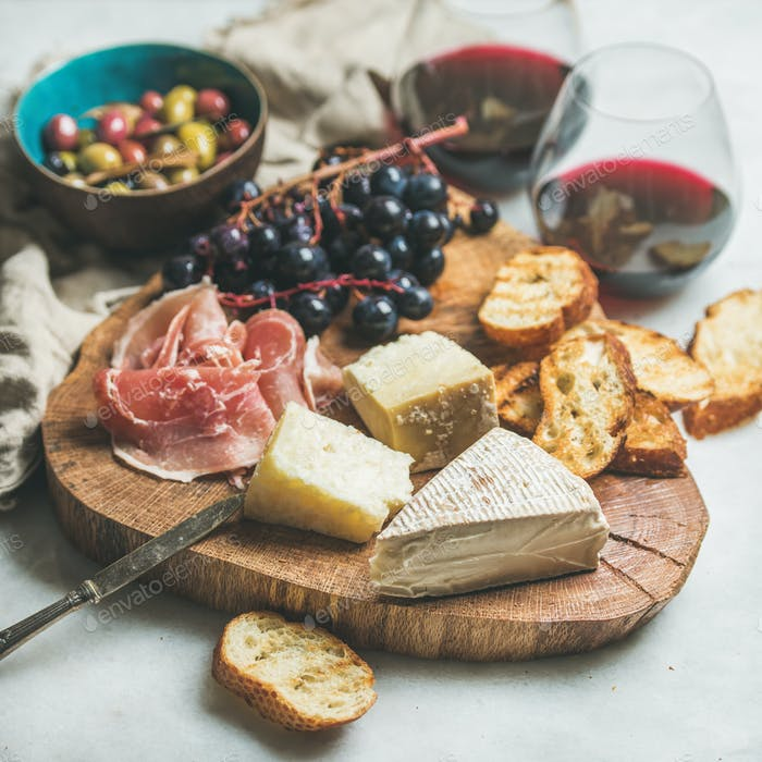 Red wine and snack variety on wooden board