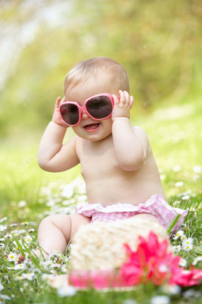 Baby Girl In Summer Dress Sitting In Field Wearing Sunglasses