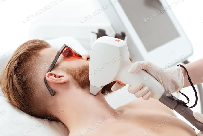young man receiving laser skin care on face. healthy lifestyle man concept