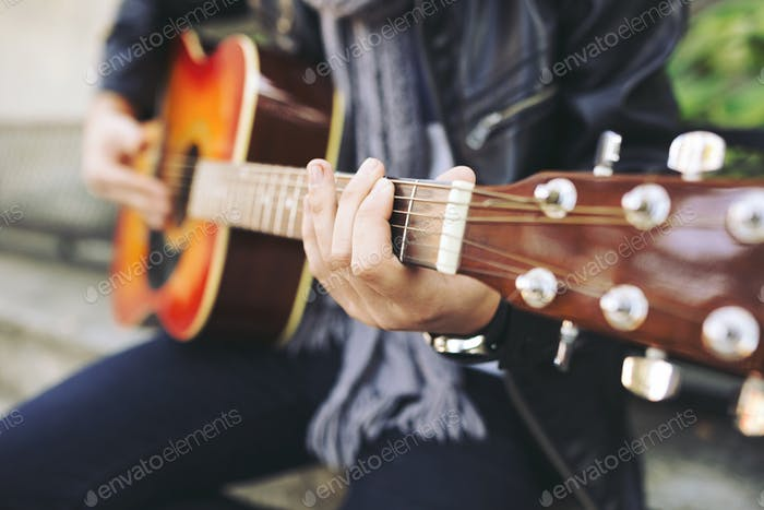 Young attractive street artist with his guitar