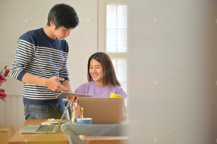 Male and female students are consulting projects for teacher presentations with tablets and laptops.
