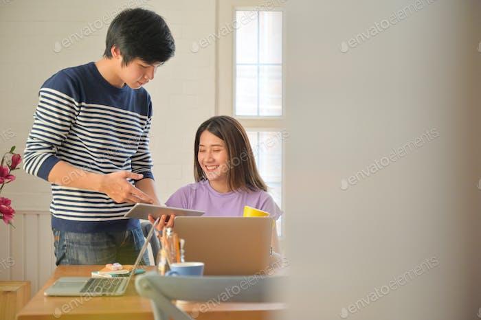 Männliche und weibliche Studierende beraten Projekte für Lehrerpräsentationen mit Tablets und Laptops.