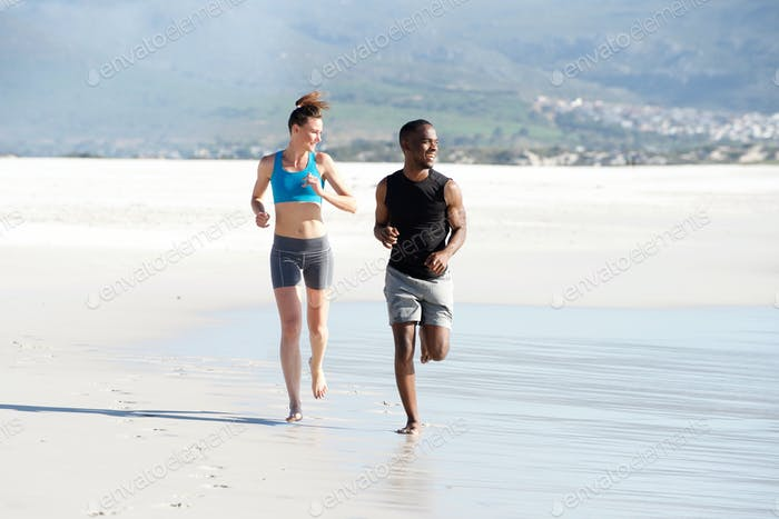 Happy young mixed race couple running on the seashore