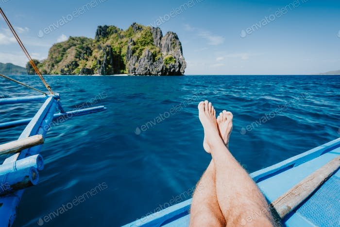 Man feet banca boat deck approaching tropical island. Travel, summer exotic vacation holidays