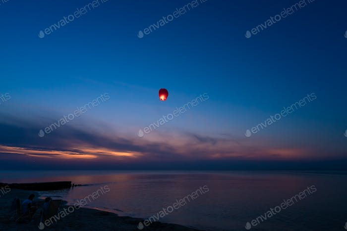 Chinese lantern flying over the calm sea at night