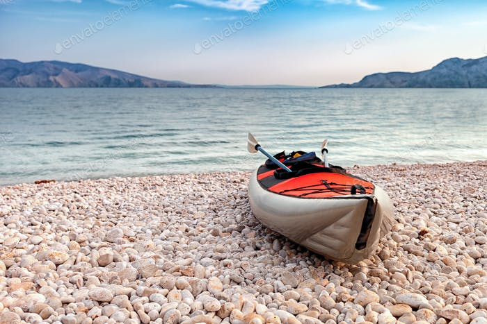 Empty kayak on beach over sea bay landscape, background with copyspace