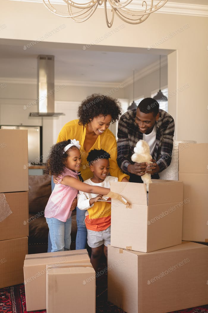 Happy parents with their children packing their belongings in living room at home