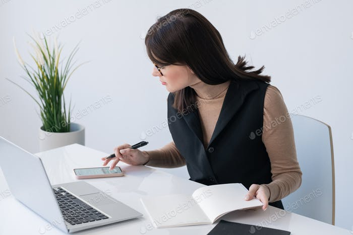 Young successful businesswoman with open copybook scrolling in smartphone