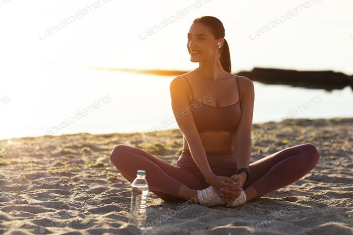 Happy yogi woman sitting in butterfly pose, listening to music