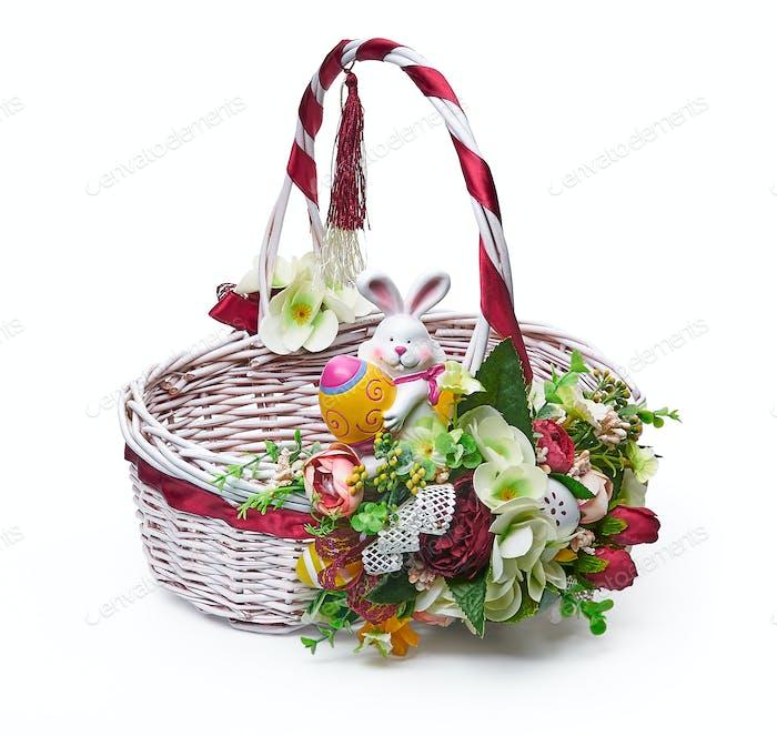 Festlicher Korb mit Blumenarrangement auf weißem Hintergrund