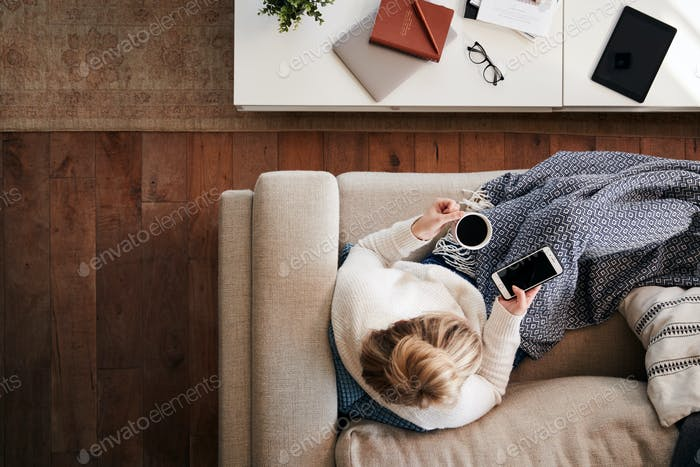 Overhead Shot Looking Down On Woman At Home Lying On Sofa Using Mobile Phone