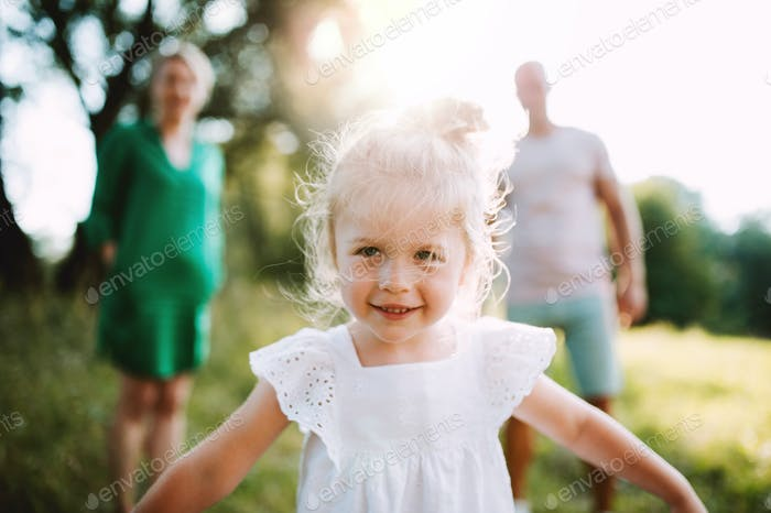 A small girl with unrecognizable parents in sunny summer nature.