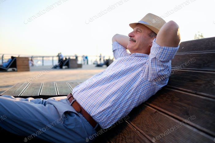 Senior hispanic man in summer hat sitting outdoors on bench.