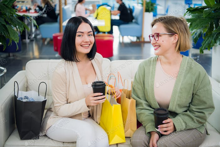 Portrait of smiling women with shopping bags and coffee to go looking at camera at the shopping mall