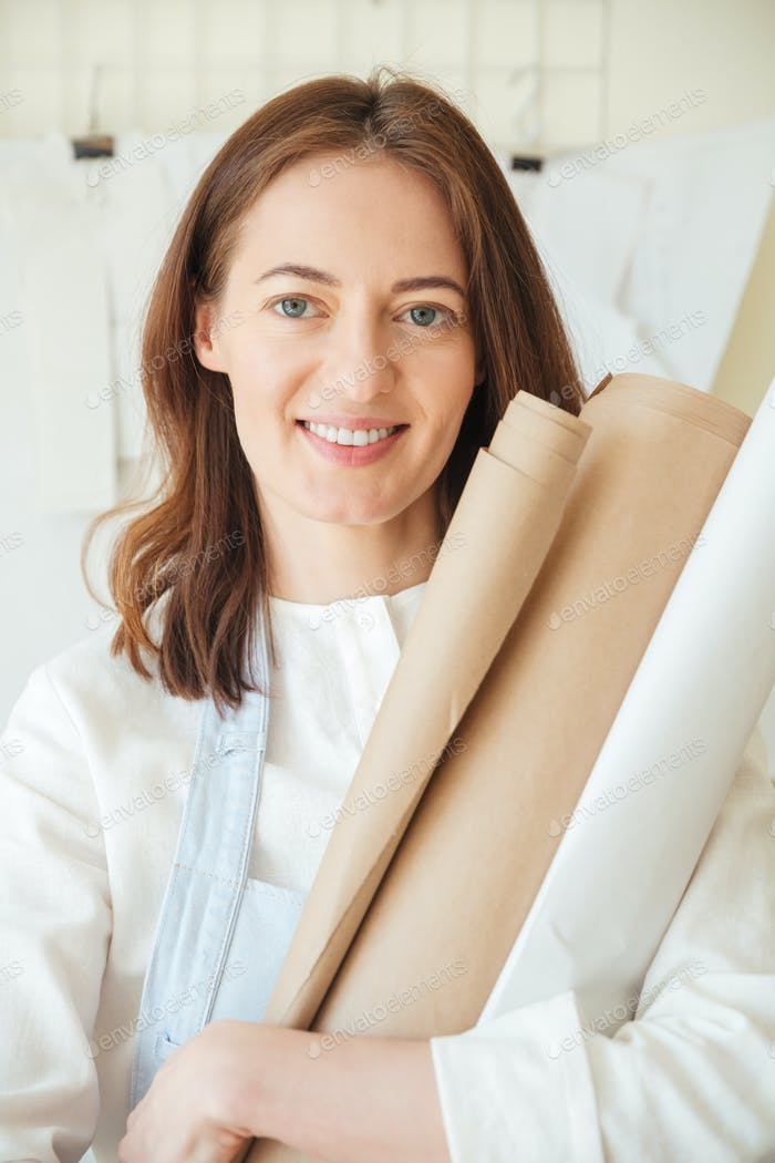 Smiling woman holding rolls of craft paper