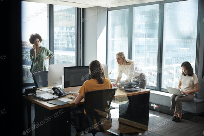 Four female creative colleagues working together in an office, seen through glass with reflection