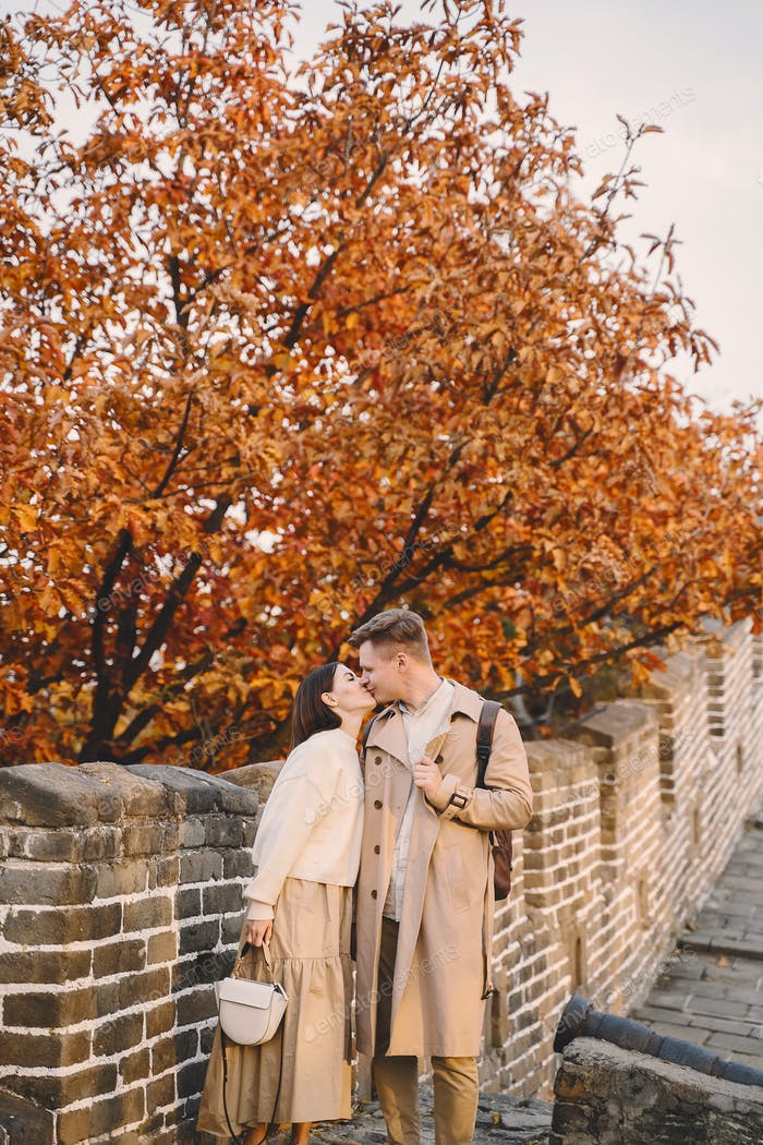 young couple kissing at the Great Wall of China