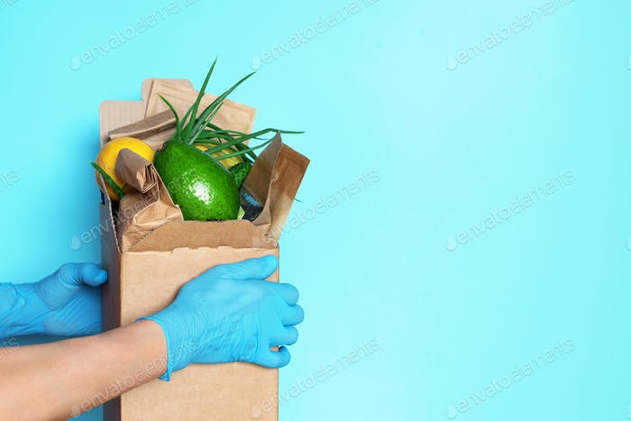 Food delivery service during coronavirus pandemic. Hands in medical gloves carrying package box of