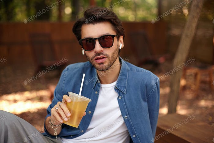 Beautiful young bearded male looking to camera with serious face, drinking juice