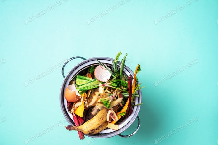 Peeled vegetables on chopping board, white compost bin on blue background. Top view of kitchen food