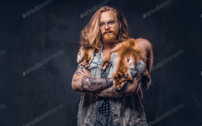 Portrait of a tattooed redhead hipster male holds a keeps the scarecrow of an owl in a studio