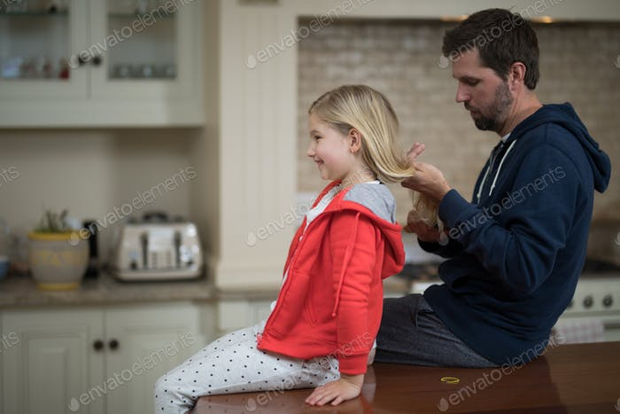 Father making daughters hairstyle