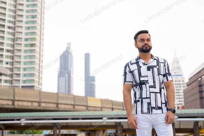Young bearded Indian man thinking against view of sky train station