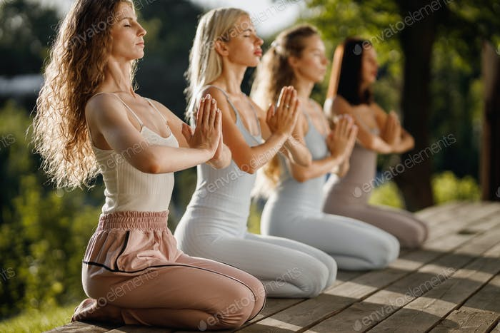 Four young girls are practising yoga sitting on the wooden podium in the garden with folded hands