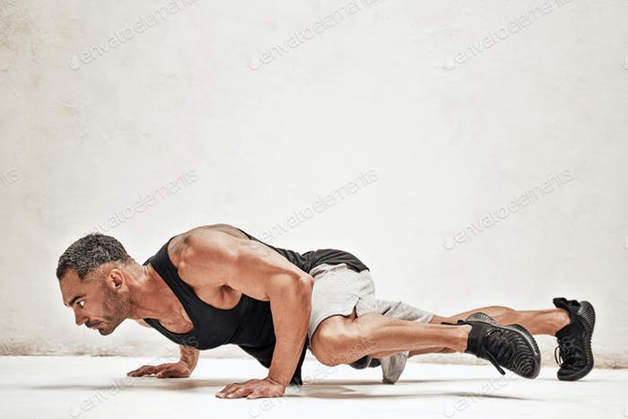 Buffed sportsman posing in a bright studio, while doing an exercise on the floor