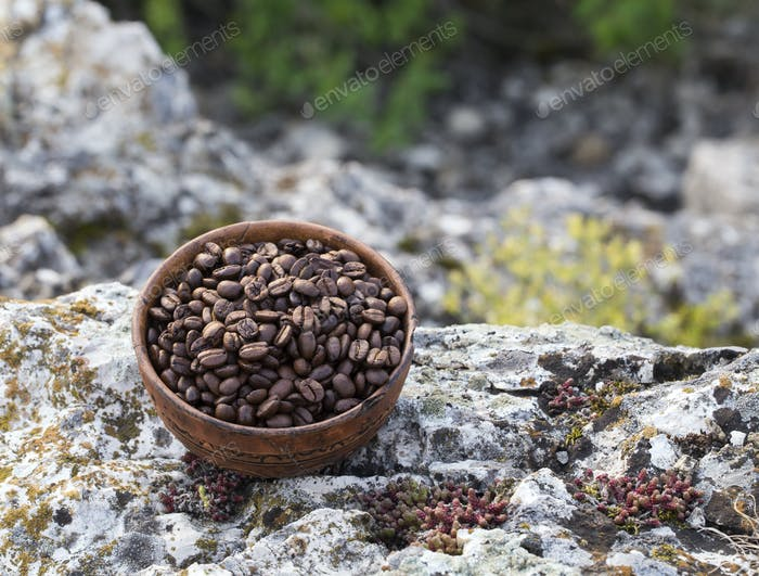 Coffee beans into ceramic bowl.