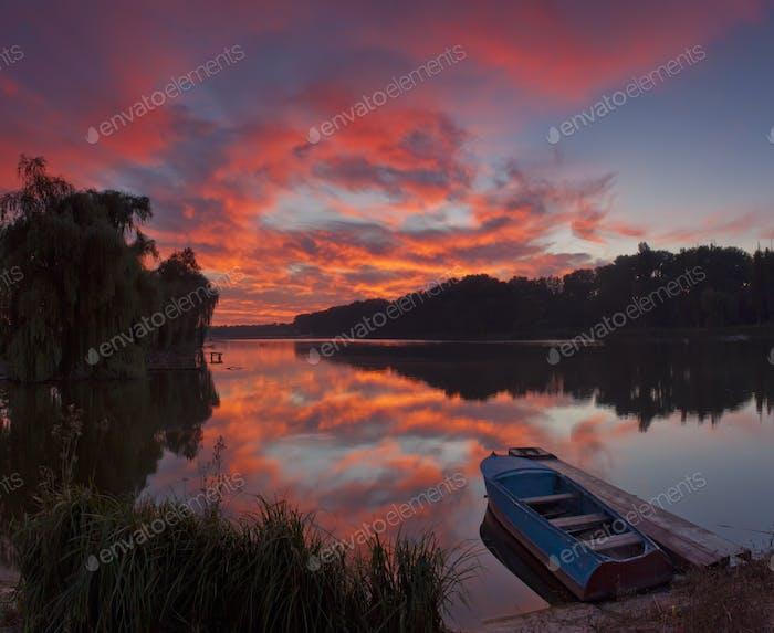 Panorama of beautiful dawn on lake with boat