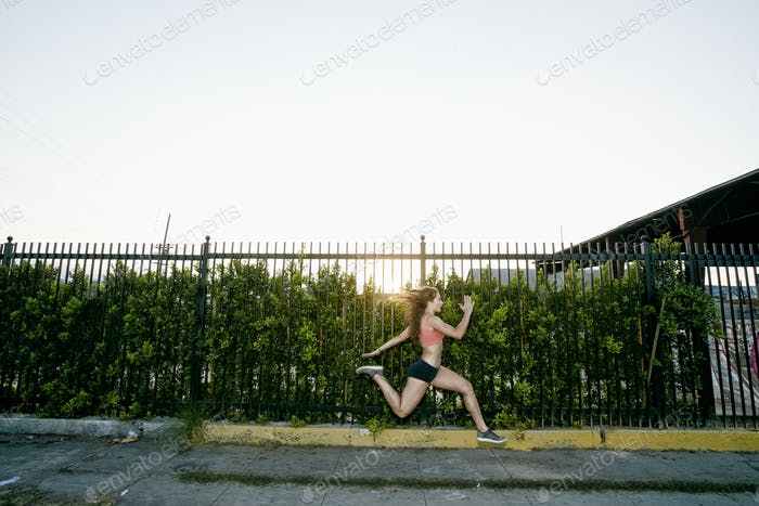Sportlerin läuft in der Abenddämmerung entlang der Straße.