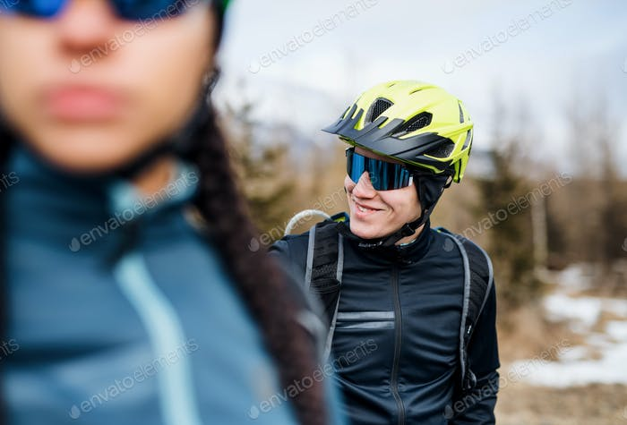 Two mountain bikers standing on road outdoors in winter