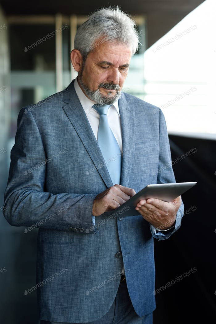 Senior businessman with tablet computer outside of modern office