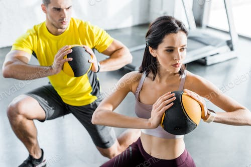 sportsman and sportswoman doing lunges with balls in sports center
